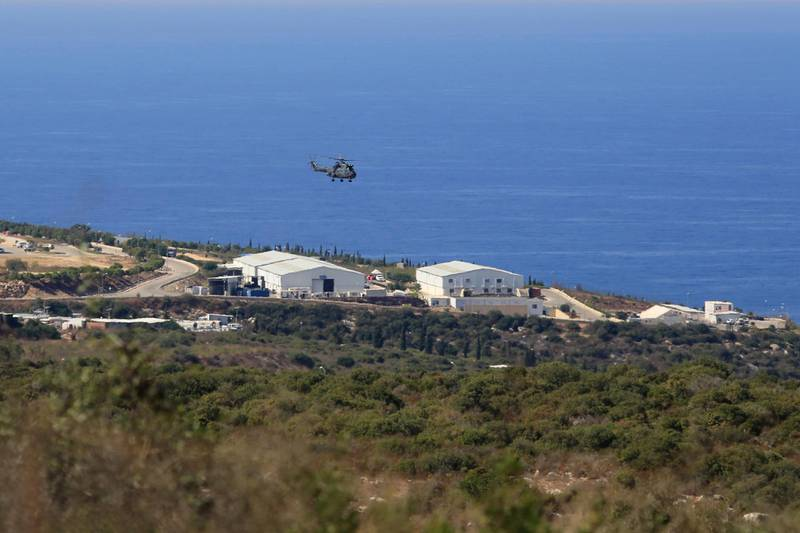 FILE - In this Oct. 14, 2020 file photo, a helicopter flies over a base of the U.N. peacekeeping force, in the southern town of Naqoura, Lebanon. On Wednesday, Oct. 28, 2020, Lebanon and Israel held a second round of U.S.-mediated talks over their disputed maritime border and agreed on a third meeting. The U.S.-mediated talks are being held in a tent at the U.N. post along the border known as Ras Naqoura, on the edge of the Lebanese border town of Naqoura. (AP Photo/Bilal Hussein, File)