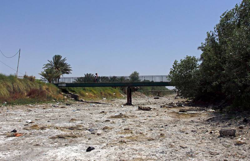 This picture shows an empty riverbed in Umm Abbasiyat, some 60 kilometers east of Najaf, on July 5, 2018. - Beyond this year's dramatic lack of rain, experts say a central reason for Iraq's creeping drought is the regional sharing of its water resources. Neighbouring Turkey and Iran in recent years have both rerouted cross-border water sources they share with Iraq. (Photo by Haidar HAMDANI / AFP)