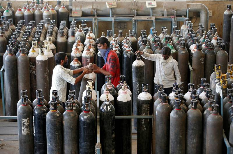People carry oxygen cylinders after refilling them in a factory, amidst the spread of the coronavirus disease (COVID-19) in Ahmedabad, India, April 25, 2021. REUTERS/Amit Dave
