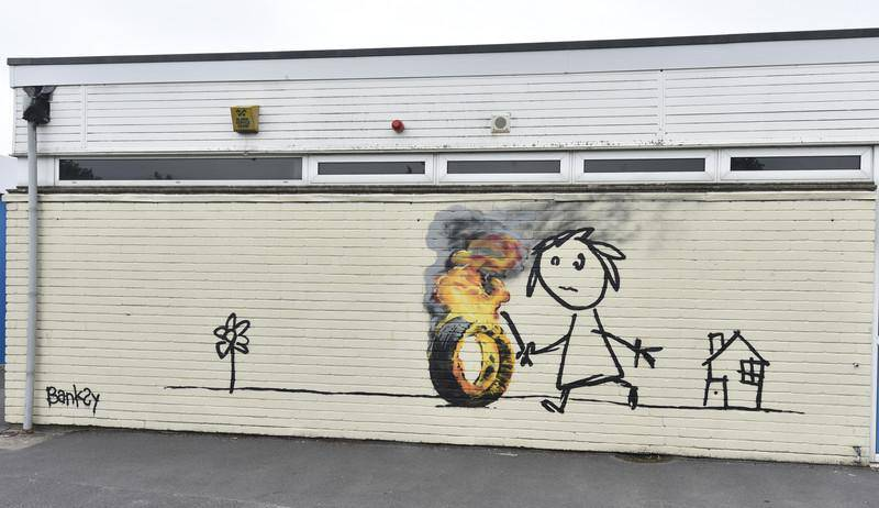 epa05349563 The Bridge Farm Primary School where a new 'Banksy' authenticated mural appeared on the school wall during half term in Withchurch, Britian, 07 June 2016. The mural, which has been authenticated by the artist PR is a thanks to the school for naming a school wing after him.  EPA/NEIL MUNNS