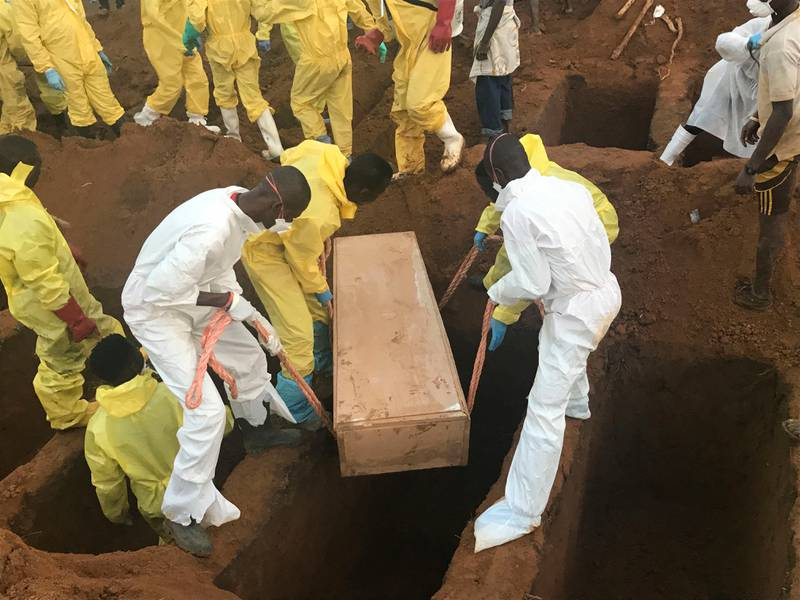 Volunteers handle a coffin during a mass funeral for victims of heavy flooding and mudslides in Regent at a cemetery in Freetown, Sierra Leone, Thursday, Aug. 17, 2017. The government has begun burying the hundreds of people killed earlier this week in mudslides in Sierra Leone's capital, and it warned Thursday of new danger from a large crack that has opened on a mountainside where residents were told to evacuate. (AP Photo/ Manika Kamara)