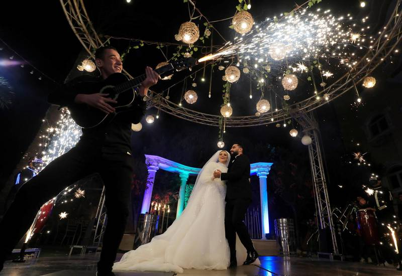 Groom Moustafa Khaled and bride Hager Yasser dance as a live band performs, during their traditional wedding celebration at the outdoor Grand Palace villa in Queisna, as Egyptian government only allows outdoor events amid the coronavirus disease (COVID-19) pandemic, in Egypt's northern Nile Delta province of Menoufia, Egypt November 4, 2020. REUTERS/Amr Abdallah Dalsh