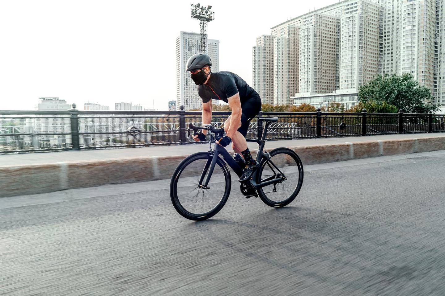 Athletic sportsman riding professional bike in race on a road on concrete bridge. Cyclist on professional bicycle training day. Concept of active lifestyle and outdoor hobby.