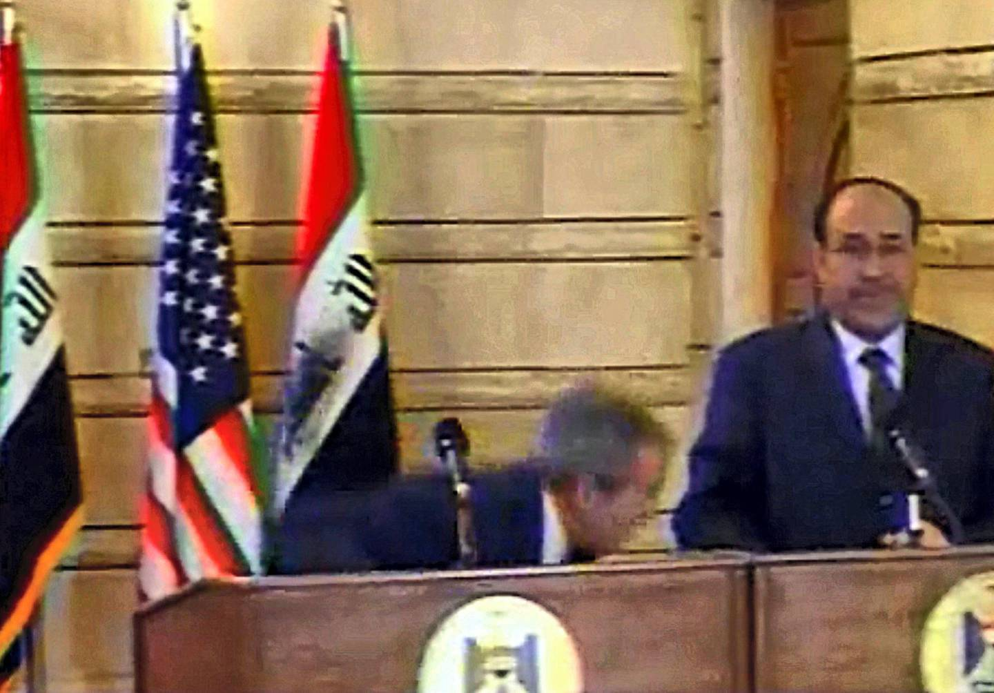 """An image grab taken from footage broadcast by the Al-Arabiya news channel shows US President George W. Bush (L) reacting as an Iraqi journalist hurls one of his shoes at him during a joint press conference with Iraqi Prime Minister Nuri al-Maliki (R) in Baghdad on December 14, 2008. Muntazer al-Zaidi from Al-Baghdadia channel hurled his shoes and an insult at Bush, without hitting him, as the US president was shaking hands with the Iraqi premier at his Baghdad office today. Zaidi jumped up, shouting: """"It is the farewell kiss, you dog,"""" and threw his shoes one after the other towards Bush. Maliki made a protective gesture towards the US president, who ducked and was not hit. AFP PHOTO/DSK == RESTRICTED TO EDITORIAL USE == / AFP PHOTO / AL-ARABIYA"""