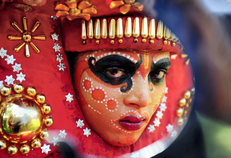 An Indian 'Theyyam' artist with his face painted waits to perform during the 'Kummati Kali' as part of the annual Onam festival celebrations in Thrissur district of southern Kerala state on September 15, 2016. - The Theyyam worship rituals are part of several thousand year-old traditions and customs celebrated in Kerala state. (Photo by ARUN SANKAR / AFP)