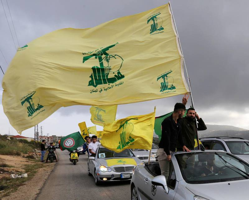 FILE PHOTO: A supporter of Lebanon's Hezbollah gestures as he holds a Hezbollah flag in Marjayoun, Lebanon May 7, 2018. REUTERS/Aziz Taher//File Photo