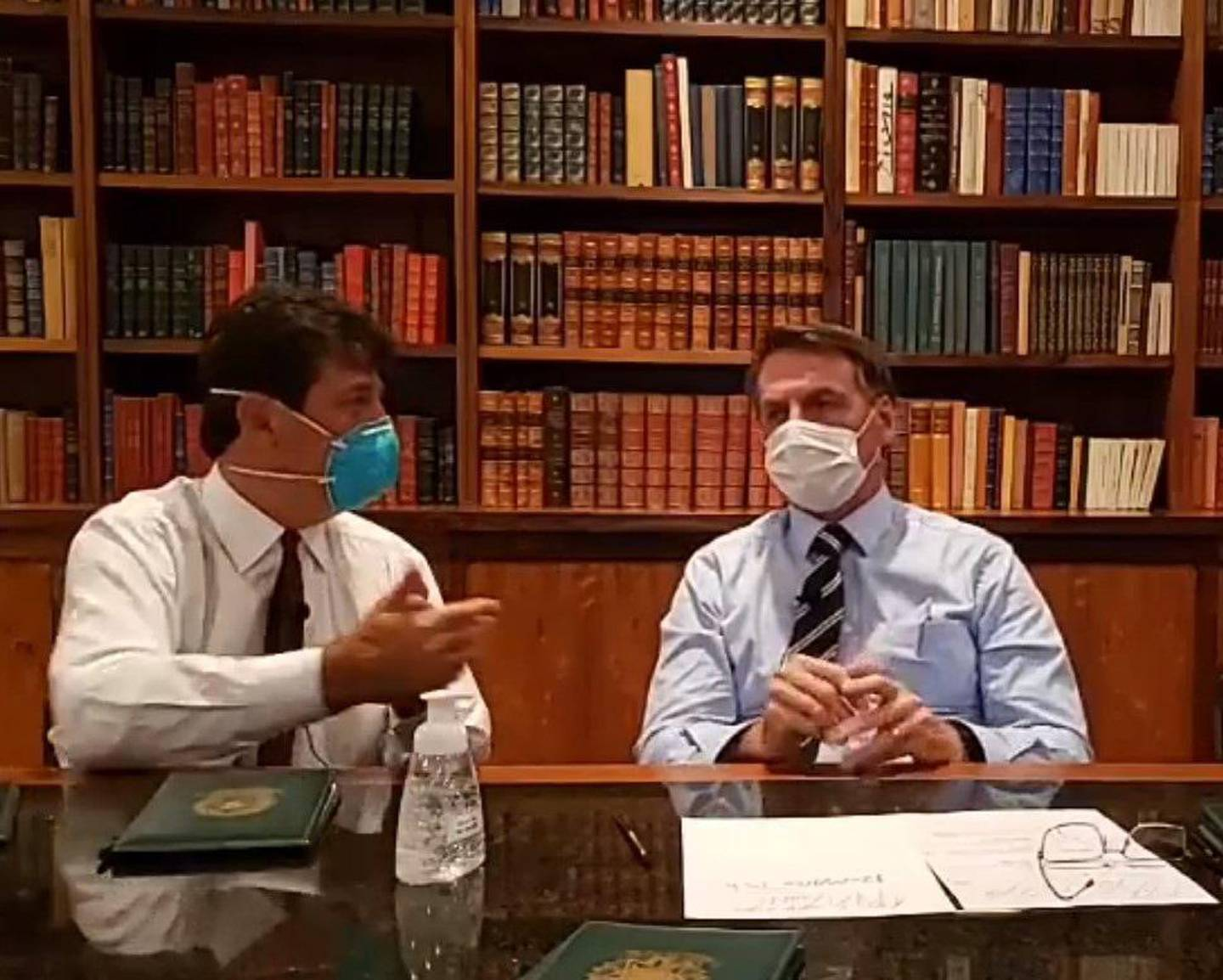 epa08290904 A grab from a video made available by official account of the President of Brazil Jair Bolsonaro which shows President of Brazil Jair Bolsonaro (R) and Brazilian Minister of Health, Luiz Henrique Mandetta (L) while participating in a video published on his channel, while remaining in isolation, at the Palacio de la Alvorada, in Brasilia , Brazil, 12 March 2020. Brazilian President Jair Bolsonaro is awaiting test results to determine if he contracted the coronavirus after one of his close associates tested positive, but he has no symptoms of the disease, clarified this Thursday one of his sons, Deputy Eduardo Bolsonaro.  EPA/Jair Bolsonaro / HANDOUT  HANDOUT EDITORIAL USE ONLY/NO SALES