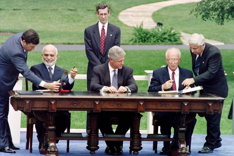 Israeli Prime Minister Yitzhak Rabin (2nd R) and Jordan's King Hussein (2nd L) are directed where to sign by unidentified aides as US President Bill Clinton (C) looks on during ceremonies at the White House in Washington, on July 25, 1994. - Prime Minister Rabin and King Hussein signed a declaration of peace designed to end 46 years of hostility between their countries. (Photo by Paul J. RICHARDS / AFP)