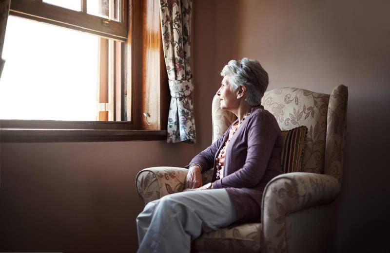 Shot of a senior woman sitting alone in her living room. Getty Images