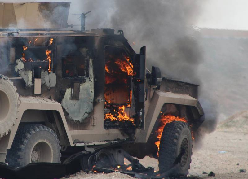 A military vehicle is on fire at the scene of a suicide car bomb attack on a military convoy on a road in Syria's northeastern Hasakeh province, which killed five members of a Kurdish-led force accompanying US-led coalition troops on January 21, 2019. The attack, claimed by the Islamic State group, killed five members of a Kurdish-led force accompanying US troops in an anti-jihadist coalition, according to the Syrian Observatory for Human Rights monitoring group. / AFP / -