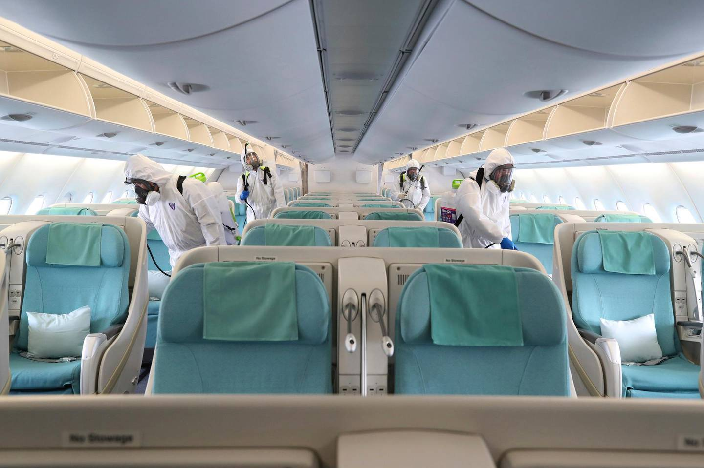 Workers wearing protective gears spray disinfectant inside an airplane for New York as a precaution against the new coronavirus at Incheon International Airport in Incheon, South Korea, Wednesday, March 4, 2020. The coronavirus epidemic shifted increasingly westward toward the Middle East, Europe and the United States on Tuesday, with governments taking emergency steps to ease shortages of masks and other supplies for front-line doctors and nurses. (Suh Myoung-geon/Yonhap via AP)