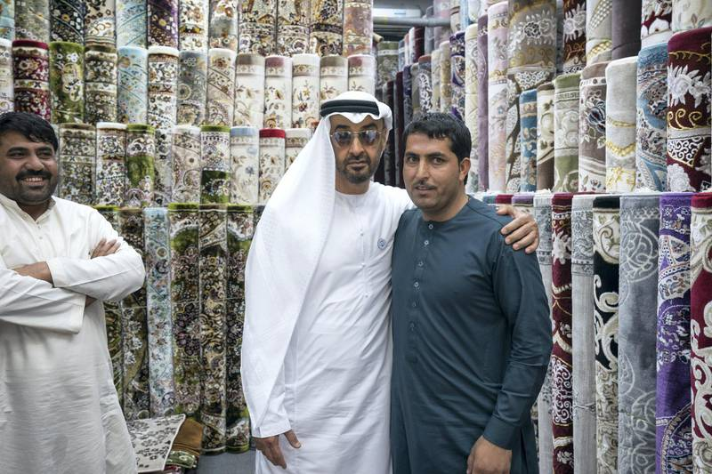 ABU DHABI, UNITED ARAB EMIRATES -  February 22, 2018: HH Sheikh Mohamed bin Zayed Al Nahyan, Crown Prince of Abu Dhabi and Deputy Supreme Commander of the UAE Armed Forces (center L), stands for a photograph with staff at Al Safa Carpet shop, in the carpet market of the Mina Zayed Port.  ( Ryan Carter for the Crown Prince Court - Abu Dhabi ) ---