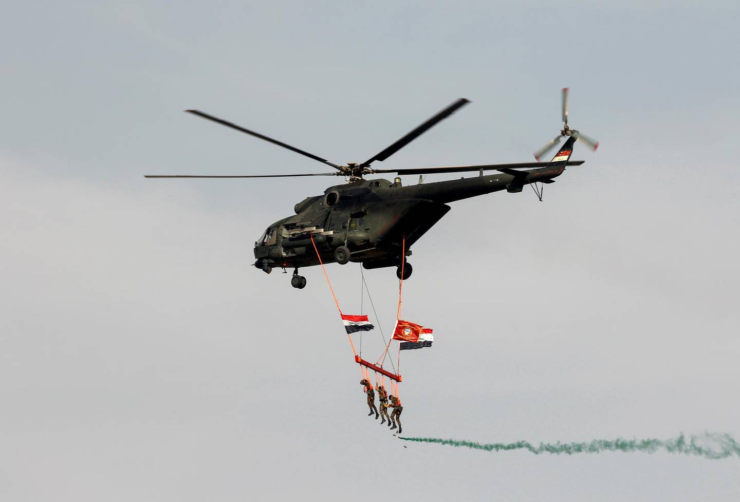 A military helicopter flies with Iraqi special forces soldiers hanging onto a rope and displaying Iraqi flags in Baghdad, Iraq April 6, 2021. REUTERS/Khalid al-Mousily