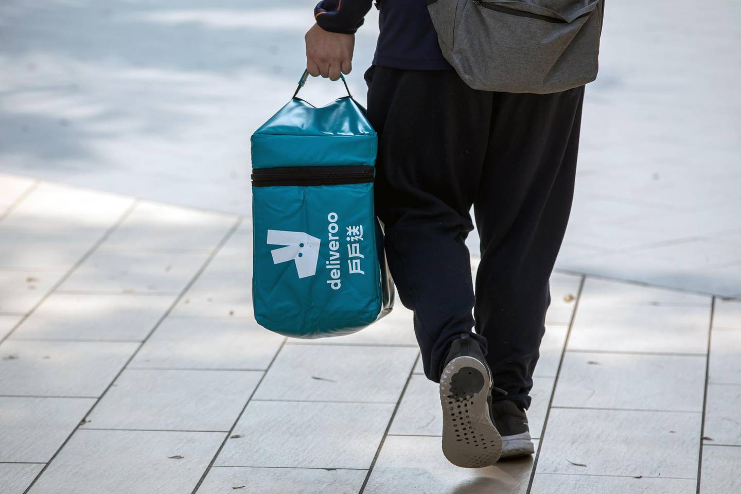 A Deliveroo food delivery worker carries an insulated food bag in Hong Kong, China, on Thursday, Feb. 20, 2020. A group of 59 Hong Kong police officers are being quarantined after a fellow officer preliminarily tested positive for the virus, the city's police force said in a statement on Facebook. Photographer: Paul Yeung/Bloomberg