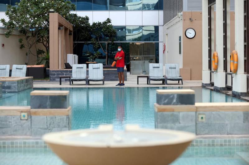 Dubai, United Arab Emirates - Reporter: N/A. Standalone. Covid-19/Coronavirus. Lifeguard Mamun watches over the pool with a face mask at the H Hotel in Dubai. Thursday, August 27th, 2020. Dubai. Chris Whiteoak / The National