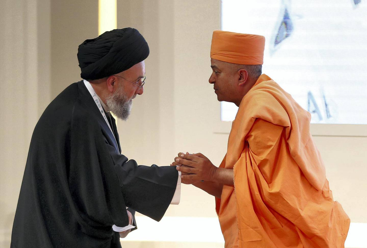 Abu Dhabi, United Arab Emirates - February 03, 2019: H.E. Swami Brahmavihari and H.E. Ali Al-Amin shake hands in the second session at the Global Conference of Human Fraternity. Sunday the 3rd of February 2019 at Emirates Palace, Abu Dhabi. Chris Whiteoak / The National