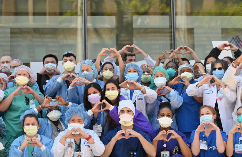 Nurses and healthcare workers gesture hearts in celebration of Nurse Week and International Nurses Day outside Mt. Sinai Oueens in the Queens borough of New York City on May 12, 2020. (Photo by Angela Weiss / AFP)