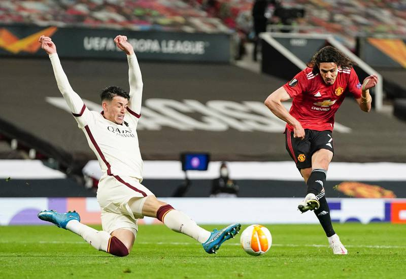 Manchester United's Edinson Cavani, right, kicks the ball during the Europa League semi final, first leg soccer match between Manchester United and Roma at Old Trafford in Manchester, England, Thursday, April 29, 2021. (AP Photo/Jon Super)