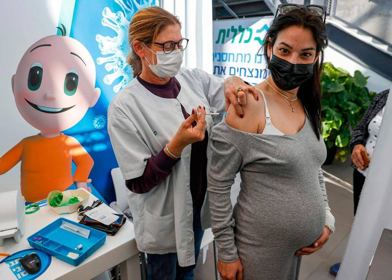 A health worker administers a dose of the Pfizer-BioNtech COVID-19 coronavirus vaccine to a pregnant woman at Clalit Health Services, in Israel's Mediterranean coastal city of Tel Aviv on January 23, 2021.  Israel began administering novel coronavirus vaccines to teenagers as it pushed ahead with its inoculation drive, with a quarter of the population now vaccinated, health officials said. / AFP / JACK GUEZ