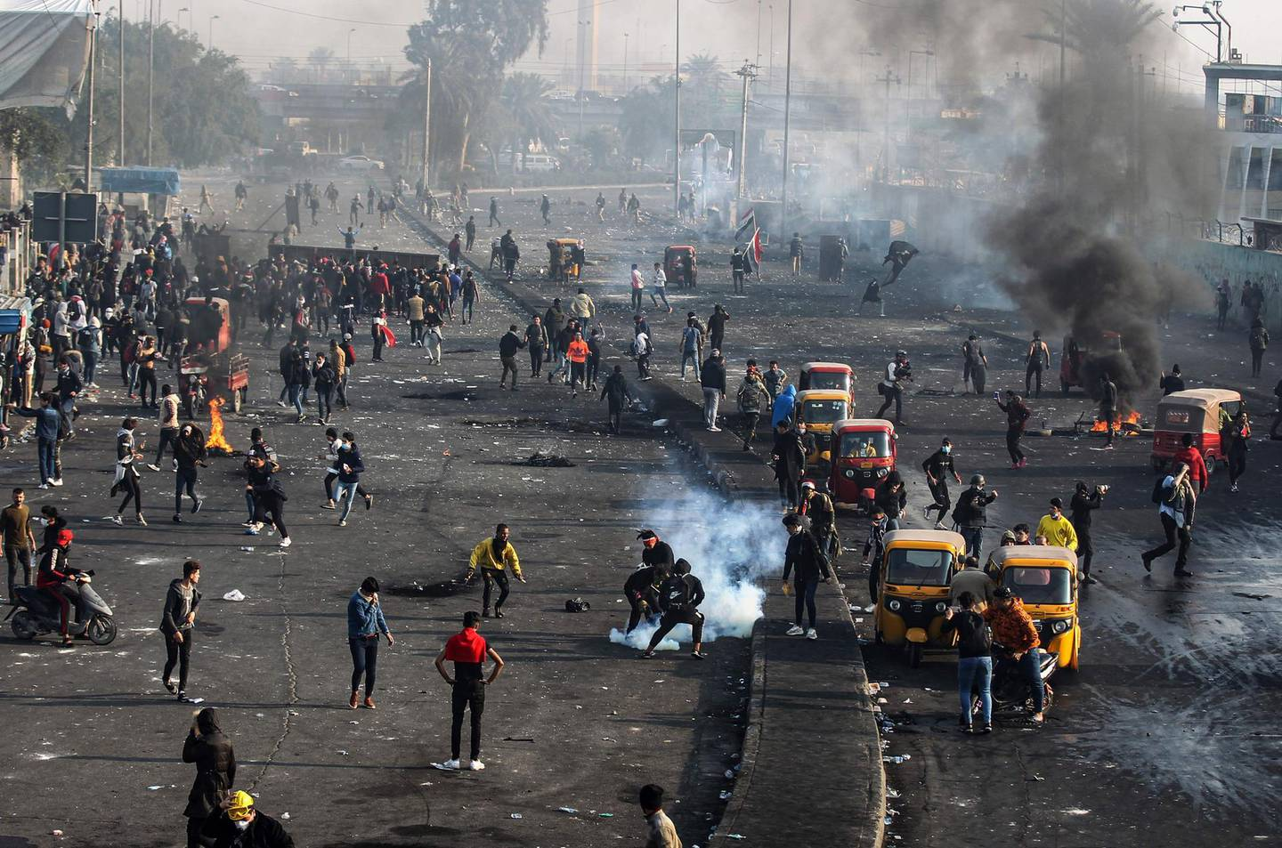 This picture taken on January 20, 2020 shows a view of clashes between Iraqi security forces (background) and anti-government protesters (foreground) as tuktuks (motorised rickshaws) are present on the scene to transport the injured, at Tayaran Square, east of Tahrir Square in the centre of the capital Baghdad.  / AFP / AHMAD AL-RUBAYE
