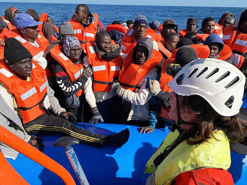 In this photo taken on Saturday, Jan. 19, 2019, rescued migrants are assisted by Sea-Watch rescue ship's personnel in the Mediterranean Sea. A private rescue boat with dozens of migrants aboard sought permission for a second day to enter a safe port Sunday, but said so far its queries to several nations haven't succeeded. Another vessel crowded with panicking migrants and taking on water, meanwhile, put out an urgent, separate appeal for help in the southern Mediterranean. Sea-Watch 3, run by a German NGO, said Sunday it has contacted Italy, Malta, Libya as well as the Netherlands, since the boat is Dutch-flagged, asking where it can bring the 47 migrants it had taken aboard. Sea-Watch tweeted that Libyan officials had hung up when it asked for a port assignment. (Doug Kuntz/Sea-Watch via AP)