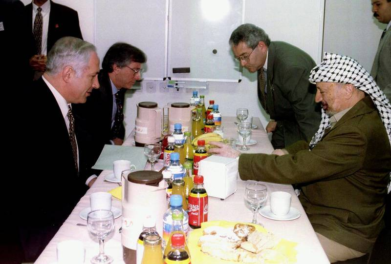 Israeli Prime Minister Benjamin Netanyahu (L) and Palestinian President Yasser Arafat (R) during their meeting at Erez Crossing point, northen Gaza Strip, December 24. Arafat and Netanyahu met here in search of an agreement to end Israeli occupation of Hebron and revive the peace process. In the background at left is U.S. mediator Dennis Ross.