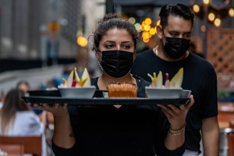 A worker wears a protective mask while carrying a tray with food in the outside dining area of Crown Shy restaurant in New York, U.S., on Saturday, Sept. 26, 2020. New York City currently prohibits all indoor dining, but will allowrestaurantsto open indoor dining rooms at 25% capacity,beginningSeptember 30. Photographer: David 'Dee' Delgado/Bloomberg