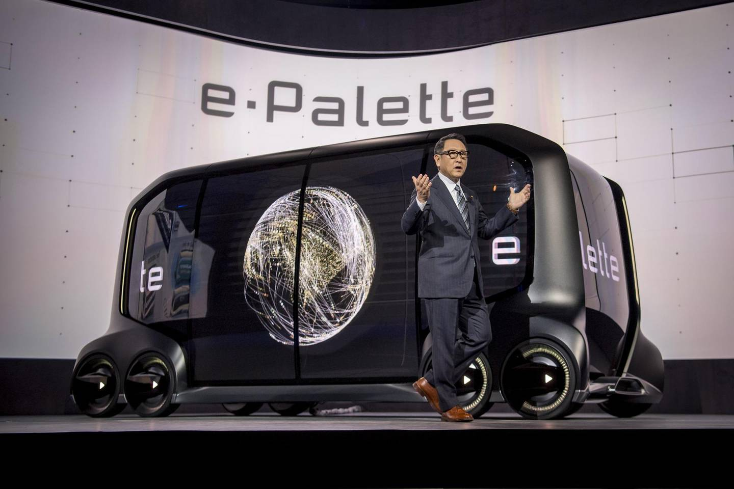 Akio Toyoda, president of Toyota Motor Corp., stands in front of the e-Palette concept vehicle while speaking during the company's press conference at the 2018 Consumer Electronics Show (CES) in Las Vegas, Nevada, U.S., on Monday, Jan. 8, 2018. Toyota Motor Corp., trying to transform itself into a leader of the new driverless economy, unveiled both the concept vehicle and the big-name partners to make it a reality. Photographer: David Paul Morris/Bloomberg