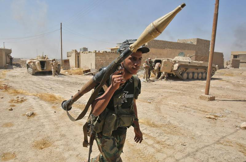 A fighter from the Hashed Al-Shaabi (Popular Mobilization units) carries his RPG inside al-Nour neighbourhood, in eastern Tal Afar, the main remaining stronghold of the Islamic State group, after the government announced the beginning of an operation to retake it from the jihadists, on August 23, 2017. - Iraqi forces recaptured several districts and advanced towards the centre of Tal Afar, one of the Islamic State group's last strongholds in the country, as aid workers braced for an exodus of civilians fleeing the fighting. (Photo by AHMAD AL-RUBAYE / AFP)