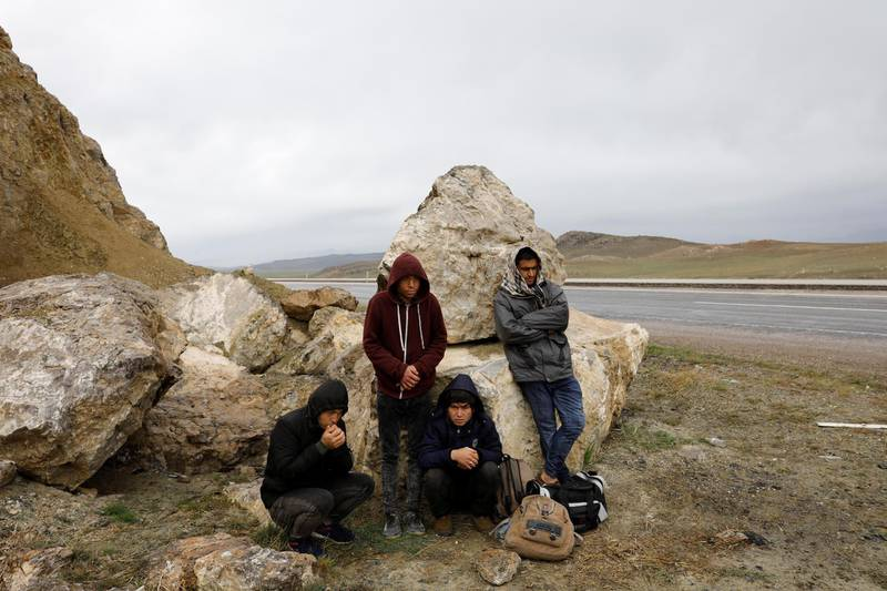 A group of Afghan migrants rest, during a break from their walk, on a main road, after crossing the Turkey-Iran border near Dogubayazit in Agri province, eastern Turkey, April 11, 2018. Picture taken April 11, 2018. REUTERS/Umit Bektas - RC1ED673F5D0
