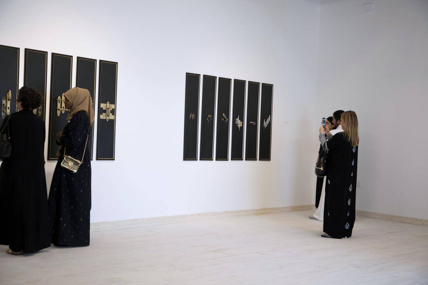 A woman takes a picture of an art work at Makan gallery in Jeddah.