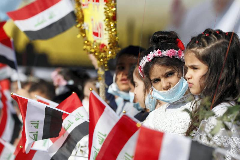 Girls wave national flags as they gather at Church square ahead of Pope Francis' arrival to visit Mosul, Iraq, March 7, 2021. REUTERS/Yara Nardi