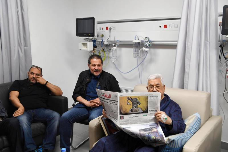 epa06754881 A handout photo made available by the Palestinian President office shows the Palestinian leader Mahmoud Abbas (R) reading the newspaper, with both sons next to him as he recovers at a hospital in Ramallah, West bank,  21 May 2018. Media report that the Palestinian President Mahmoud Abbas hospitalization for the third time in the past week has led to conflicting reports about his health.  EPA/Thaer Ghanaim HANDOUT  HANDOUT EDITORIAL USE ONLY/NO SALES