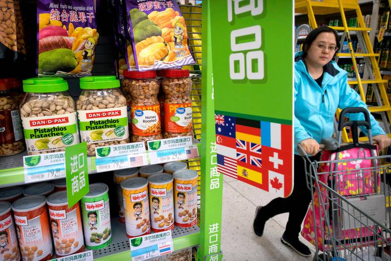 FILE - In this March 23, 2018. file photo, a woman pushes a shopping cart past a display of nuts imported from the United States at a supermarket in Beijing. China raised import duties on a $3 billion list of U.S. pork, fruit and other products Monday, April 2, 2018 in an escalating tariff dispute with President Donald Trump that companies worry might depress global commerce. (AP Photo/Mark Schiefelbein, File)