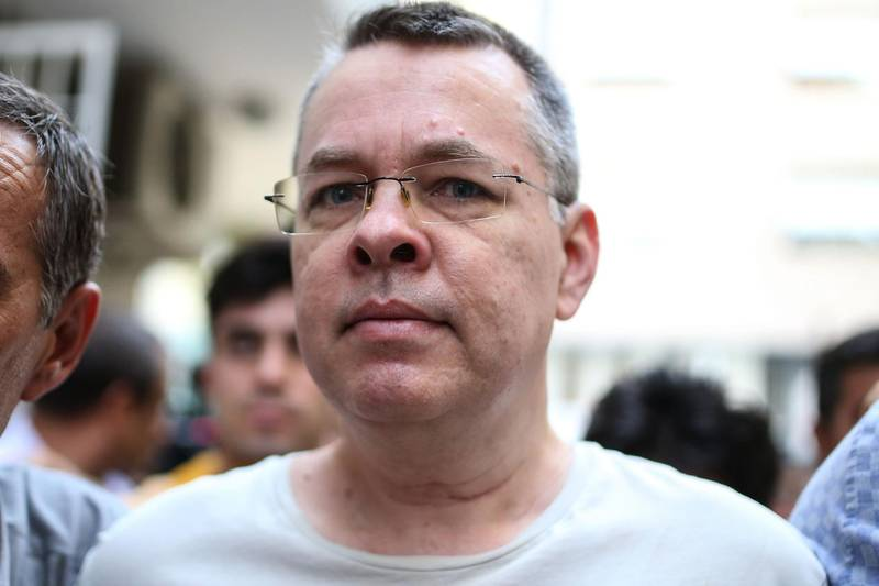 (FILES) In this file photograph taken on July 25, 2018, US pastor Andrew Craig Brunson is escorted by Turkish plain clothes police officers to his house in Izmir. - Only weeks ago it would have seemed fanciful to draw a link between the fate of an American evangelical pastor in Turkey, a crisis in bilateral ties of two NATO allies and turmoil on global financial markets. But Andrew Brunson, a Protestant clergyman who had lived in Turkey for a quarter of a century without disturbance, has now found himself at the centre of a bitter dispute between Washington and Ankara that caused the lira to crash and the economic jitters to spread globally. Brunson's world was turned upside down on October 7, 2016 when he and his wife Norine were arrested in the crackdown that followed the failed July 15 coup bid that year aimed at toppling President Recep Tayyip Erdogan. (Photo by - / AFP)