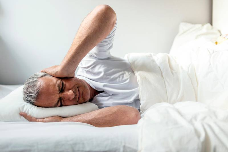 Mature Caucasian man in bed with headache lying in bed during the day. Getty Images