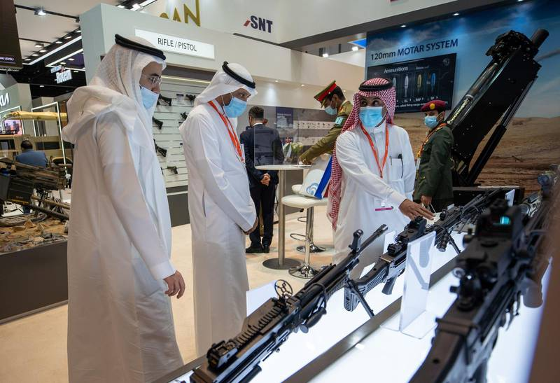 Abu Dhabi, United Arab Emirates, February 24, 2021.  Idex 2021 Day 4. Visitors look at the Korean made K-12C3 7.62mm machine gun at the SNT stand.Victor Besa / The NationalSection:  NA