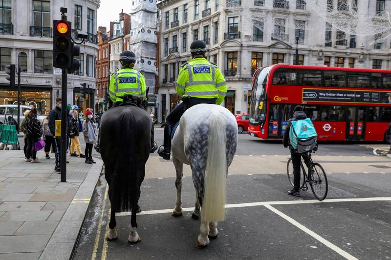 FILE PHOTO: Mounted police and a Deliveroo rider wait at a red light at Regent Street, one of London's main shopping streets, a day after a new lockdown was announced during the coronavirus disease (COVID-19) outbreak in London, Britain November 1, 2020.     REUTERS/Kevin Coombs/File Photo