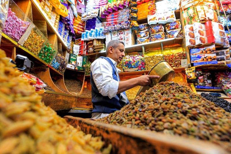 A vendor packs dried fruits and nuts for customers at an open-air market in Yemen's capital Sanaa on May 2, 2021, as Muslims prepare ahead of the Eid al-Fitr holiday marking the end of the holy fasting month of Ramadan. / AFP / Mohammed HUWAIS