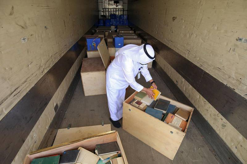 Employee at the Kuwaiti Information Ministry Essam al-Said inspects boxes in the back of a truck containing Kuwaiti archives seized during the Iraqi invasion of the Gulf emirate in 1990, after their restitution by Iraqi authorities in Kuwait City, on March 28, 2021. / AFP / YASSER AL-ZAYYAT
