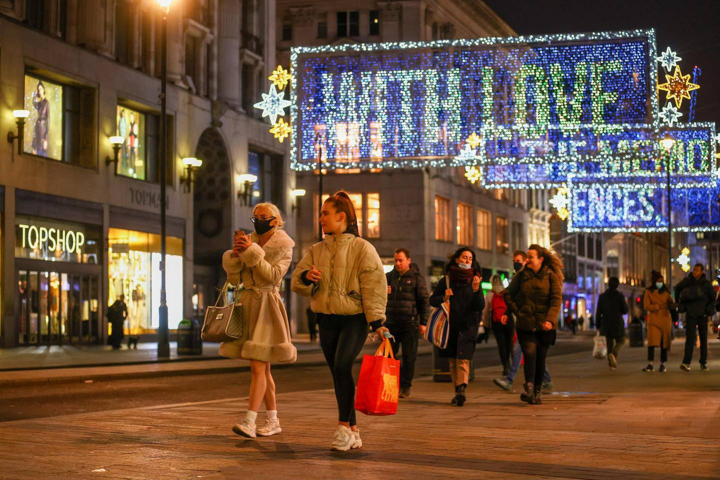 Pedestrians pass festive lights on Oxford Street in London, U.K., on Tuesday, Nov. 17, 2020. With a partial lockdown in England closing all non-essential stores until at least Dec. 2, rescuing the next six weeks from Covid-19 is critical for the U.K.'s financial well-being and a government beset by accusations that it can't get a grip on the pandemic. Photographer: Simon Dawson/Bloomberg