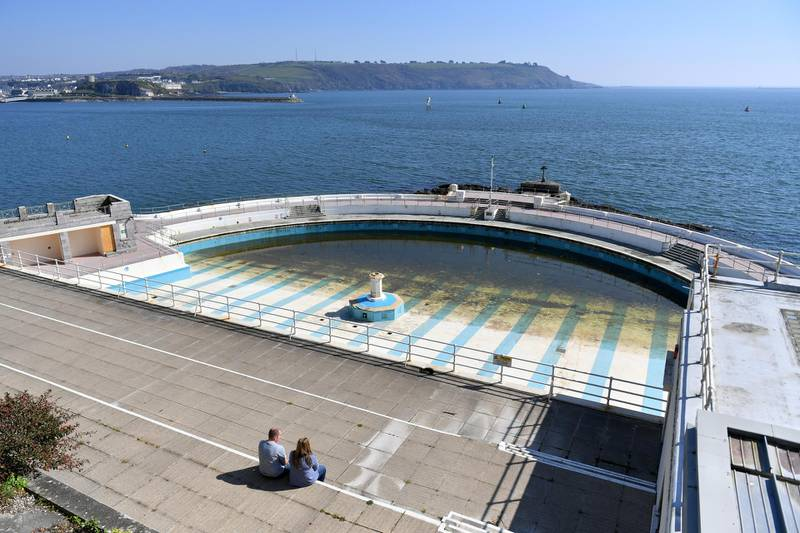 PLYMOUTH, ENGLAND - APRIL 08: A couple sit in the sunshine overlooking the closed Tinside Lido on April 08, 2020 in Plymouth, England. There have been around 50,000 reported cases of the COVID-19 coronavirus in the United Kingdom and 5,000 deaths. The country is in its third week of lockdown measures aimed at slowing the spread of the virus. (Photo by Dan Mullan/Getty Images)
