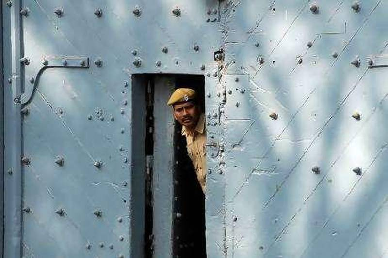 A policeman peers from inside the gate of Chanchalguda jail, where former chairman of Satyam Computer Services Ramalinga Raju is being held, in the southern Indian city of Hyderabad January 15, 2009. Raju quit last week after confessing profits had been falsely inflated for years. Raju, 54, his brother and the company's former chief financial officer have been charged and are in custody in Hyderabad, where Satyam's headquarters is located. REUTERS/Krishnendu Halder (INDIA)