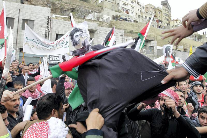 Jordanian protesters tear a dummy representing the leader of the Islamic State (IS) jihadist group, Abu Bakr al-Baghdadi (portrait), during a demonstration on February 6, 2015 in the capital Amman in solidarity with the pilot murdered by the extremist group. Thousands of people turned out after midday prayers and marched from the central al-Husseini mosque to Palm Park, about one kilometres (half a mile) away, in Amman in protest against IS. AFP PHOTO / KHALIL MAZRAAWI (Photo by KHALIL MAZRAAWI / AFP)