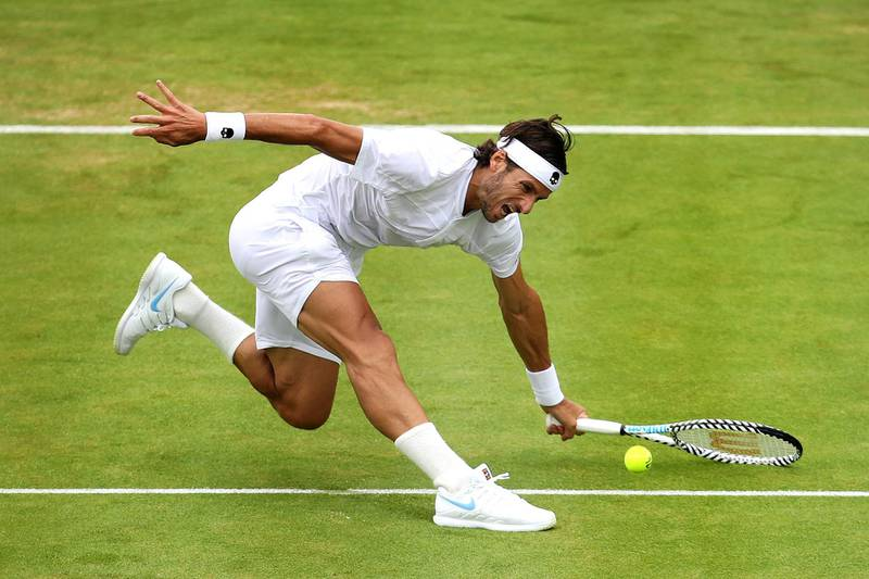 LONDON, ENGLAND - JUNE 19: Feliciano Lopez of Spain slips in attempt to play a forehand during his mens singles first round match against Marton Fucsovics of Hungary during day X of the Fever-Tree Championships at Queens Club on June 19, 2019 in London, United Kingdom. (Photo by Alex Pantling/Getty Images)