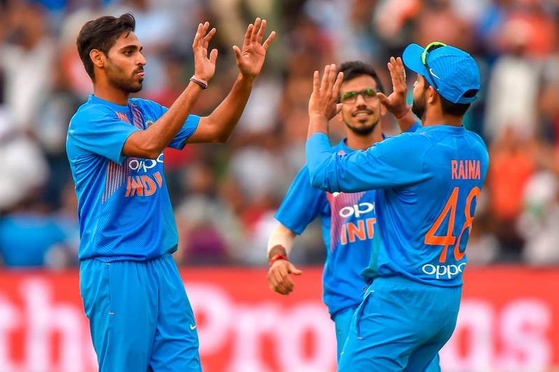 India's Suresh Raina (R) celebrates with teammate Bhuvneshwar Kumar (L) after taking a catch to dismiss unseen South African batsman Chris Morris during the first T20I cricket match between South Africa and India at The Wanderers Cricket Stadium in Johannesburg on February 18, 2018.  / AFP PHOTO / Christiaan Kotze