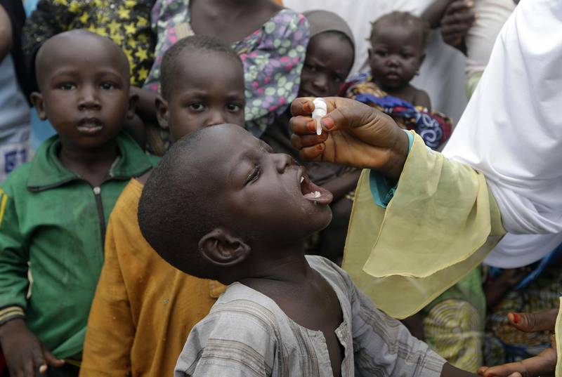 FILE - In this Sunday, Aug. 28, 2016 file photo, a health official administers a polio vaccine to children at a camp for people displaced by Islamist Extremist in Maiduguri, Nigeria. The coronavirus pandemic is interrupting immunization against diseases including measles, polio and cholera that could put the lives of nearly 80 million children at risk, according to a new analysis on Friday May 22, 2020, from the World Health Organization and partners. (AP Photo/Sunday Alamba, File)