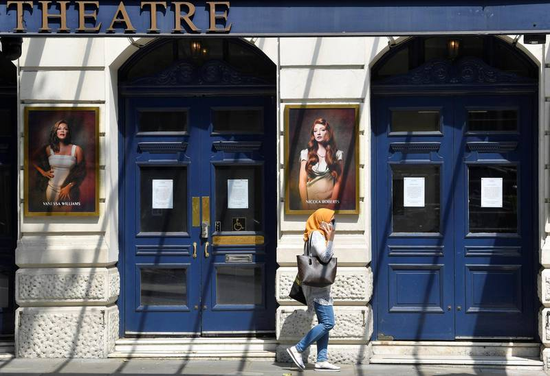 A woman wearing a protective face mask walks past a closed theatre, as the spread of the coronavirus disease (COVID-19) continues, in London, Britain June 23, 2020. REUTERS/Toby Melville