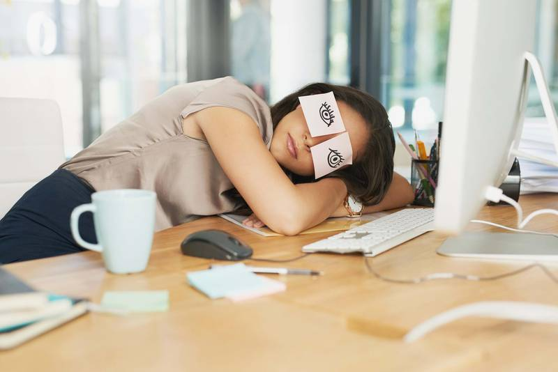 Shot of a tired businesswoman napping at her desk with adhesive notes on her eyes. Getty Images