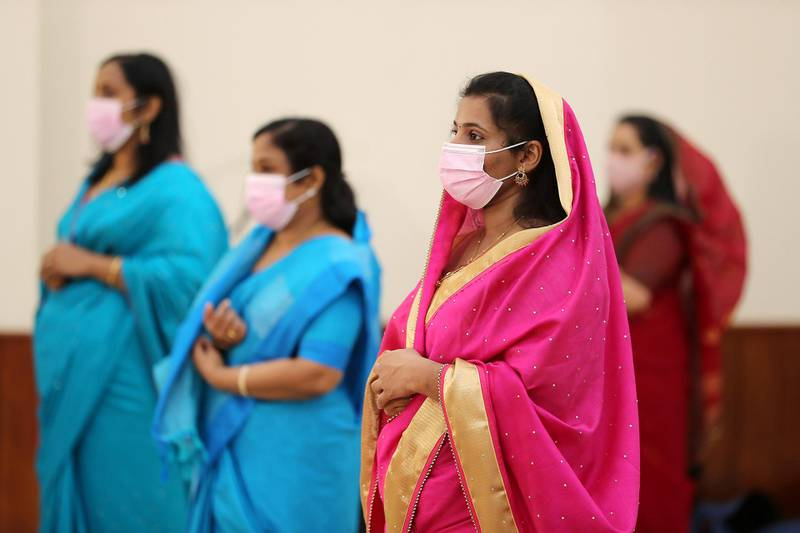 DUBAI, UNITED ARAB EMIRATES , October 26– 2020 :- Relatives and friends wearing protective face mask and gloves as a preventive measure against the spread of coronavirus and maintaining social distance during the marriage ceremony of Justin George (groom) and Jubee Vargheese (bride) held at the St. Thomas Orthodox Cathedral in Dubai.  (Pawan Singh / The National) For News/Online/Instagram. Story by Kelly
